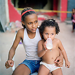 Young residents of Largo do Tanque watch a demolition of homes in their favela, in Rio de Janeiro's West Zone, to make room for the Transcarioca Highway, that will eventually be built to accommodate the Olympics, in Rio de Janeiro, Brazil, on Monday, Feb. 25, 2013. <br /> <br /> In less than 2 weeks, 54 houses were demolished with sledgehammers and bulldozers. In under 2 weeks, 54 houses were demolished and hundreds of residents left to fend for themselves. The City assessor sent to handle negotiations told residents not to speak with one another or seek legal advice otherwise he would reduce settlement offers. Many residents agreed to compensations, around R$7000 (US$3500). Most residents cannot afford to buy a plot of land with that compensation and will be forced to rent kitchenettes, at less than 20m2. As established in the Brazilian Constitution, and in accordance with local legislation (the Organic Municipal Law), the duration of residents' life in the area gave them legal rights to the homes, while compensation should allow them to attain an equal situation elsewhere. <br /> <br /> The west zone, located west of downtown and beach neighborhoods is often overlooked and is widely known to be run by militia groups, who are former and current police and firefighter personnel that run extortion rings to monopolies.
