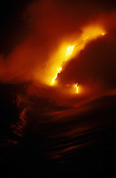 Night view of spectacular lava flows into the sea.