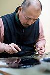 "Teruyoshi Kon decorates a fan handle with lacquer using an implement known as ""shikake-bera"" (""trick spatula"") that is used to make ""kara-nuri"" style Tsugaru lacquerware products in Hirosaki, Japan on 18 Jan. 2013. Photo: Robert Gilhooly.."