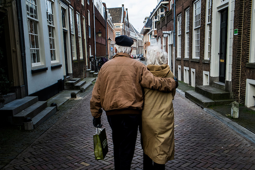 Nederland, Utrecht, 23 feb 2014<br /> Twee oudere mensen lopen door een smal straatje. Man heeft zijn arm om de vrouw geslagen.  Het straat er van af: ze houden van elkaar.<br /> <br /> Foto(c): Michiel Wijnbergh