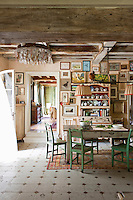 This large kitchen-diner houses a rustic wooden table and chairs arranged over a rug with the far wall covered in a collection of drawings and paintings