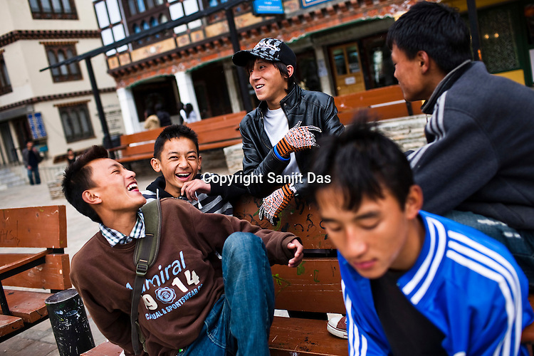 "Youths hang and share a light moment around the city's main clock tower area in downtown Thimphu, Bhutan. Television and the internet have been accessible only since 1999, and were introduced despite widespread fears that their ""controversial"" content such as fashion shows, western music, wrestling, and pornography, could destroy the kingdom's traditional way of life based on unique Buddhist principles. Sanjit Das/Panos"