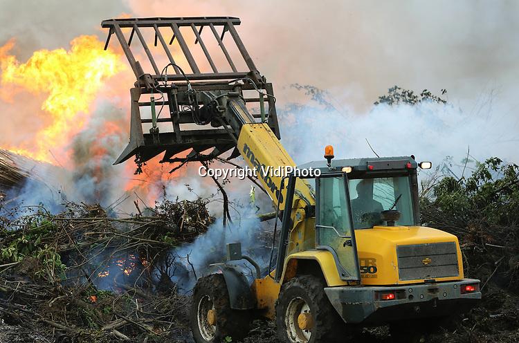 Foto: VidiPhoto<br /> <br /> OCHTEN - Een enorme vuurzee maakt duidelijk dat laanboomkwekers woensdag hun laatste kans grijpen om snoeihout te verbranden. Personeel van Huverba uit Opheusden stookt woensdag op een perceel in Ochten oude bomen, struiken en takken in de fik, om zo te besparen op het afvoeren van het groenafval. Boomkwekers krijgen daarvoor van de overheid anderhalve maand de tijd, tot 1 juni. Ze moeten vooraf wel een vergunning aanvragen. Om zoveel mogelijk snoeihout te kunnen verbranden wachten veel kwekers tot het laatste moment. En dan moet er toch gestookt worden, ook al regent het.