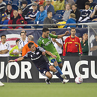 New England Revolution midfielder Ryan Guy (13) tackles Seattle Sounders midfielder Lamar Neagle (27). In a Major League Soccer (MLS) match, the Seattle Sounders FC defeated the New England Revolution, 2-1, at Gillette Stadium on October 1, 2011.