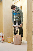 Plastering student mixes some plaster, Able Skills, Dartford, Kent.
