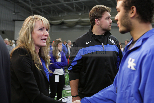 New football head coach Mark Stoops' wife, Chantell, shakes hands with some of the players during Mark Stoops' press conference in Nutter Field House in Lexington, Ky., on Sunday, December 2, 2012. Photo by Genevieve Adams | Staff