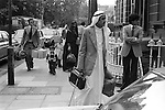 Arabs London UK 1977. Middle Eastern people came to Britain for subsidised health care in Harley Street clinics. They mainly stayed in cheap hotels in Earls Court. Arab family leaving. British helper with their bags walking towards car that takes them to the airport.