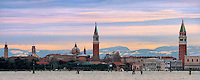 An unusual view of the Venice skyline with the snow-covered Alps in the background. Taken from the Lido about 30 minutes after sunrise on a cold and windy morning at the beginning of December