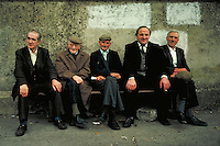 Five middle-aged Irish men while away the time on a bench. street scene. Cashel, Ireland County Tipperary.