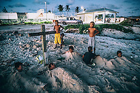 Children playing the 'Cemetery' game on one of the Ebeye's sandy beaches. The overpopulated island is informally known as the 'slum of the Pacific'. It people suffer numerous diseases and the mortality rate is one of the highest in the Republic of the Marshall Islands.