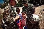 Thai military at the Thai border examine school children's book bags for drugs or other contraband. Border guards say children of Cambodians living and working in the Thai border town of Klong Yai often pass through the heavily mined &quot;White Zone&quot; between the two countries to attend school in Cambodia to maintain their language and culture