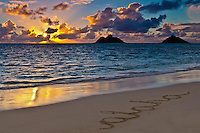 "Rays from the rising sun reflect in the water off of Lanikai Beach, Windward O'ahu; the word ""aloha"" marks the smooth sand beach in the foreground."