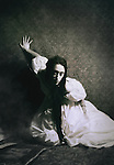A woman in a white gown, and long dark hair, kneeing in front of a decorative wall, with one hand touching the wall, and an expression of fear & misery.