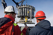 Scientists with a CTD device (Conductivity, Temperature, Depth) that is lowered and raised by a cable through the ocean to collect measurements of seawater at various depths. It also has sensors to detect chemicals and particles emanating from hydrothermal vents in the Arctic Ocean.