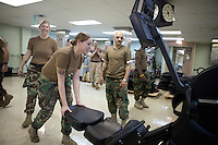 Sailors clear exercise equipment from a room to make room for patients on board the USNS Comfort, a naval hospital ship, before its mission to help survivors of the earthquake in Haiti on Tuesday, January 19, 2010.