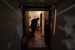 Ashton United 6 Ramsbottom United 0, 12/01/2016. Hurst Cross stadium, Northern Premier League. A groundsman sweeping a dressing room corridor after the fixture between Ashton United (in red) and Ramsbottom United in the Northern Premier League premier division. The match was played at Ashton's Hurst Cross stadium, the club's ground. The club was originally founded in 1878 as Hurst F.C. and by 1880 the club were playing at Hurst Cross, their current ground which makes their home one of the oldest football grounds in the world. Ashton won the match 6-0, watched by a crowd of 178. Photo by Colin McPherson.