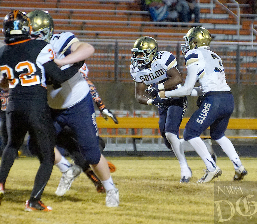 Photo by Randy Moll<br /> Connor Reece, Shiloh Christian junior quarterback, hands off the ball to Shiloh running back, John-Marcus Carruthers, a junior, during play between Shiloh Christian and Gravette at Gravette High School on Friday, Oct. 30, 2015.