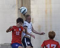 Korea Republic forward Yoo Younga (12) and USWNT defender Becky Sauerbrunn  (4) battle for head ball.  In an international friendly, the U.S. Women's National Team (USWNT) (white/blue) defeated Korea Republic (South Korea) (red/blue), 4-1, at Gillette Stadium on June 15, 2013.