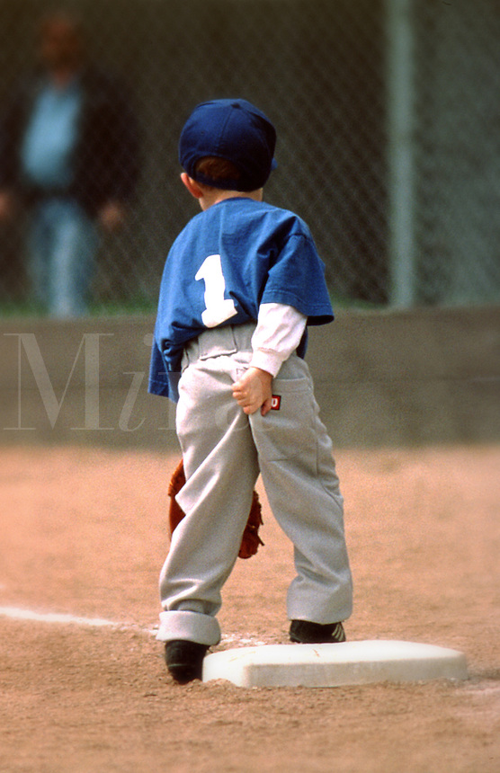 Rear view of a young baseball player in uniform scratching his bottom during a T-ball game.