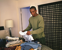 man packing a suitcase at home