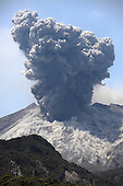 Sakurajima Volcano erupting with ash cloud rising from Showa Crater of Japan's most active volcano. Fine ash is thrown up on flanks by impact of volcanic bombs.