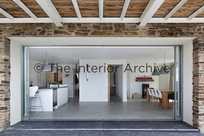 Large sliding doors in the contemporary kitchen/dining area open on to a slate-tiled terrace