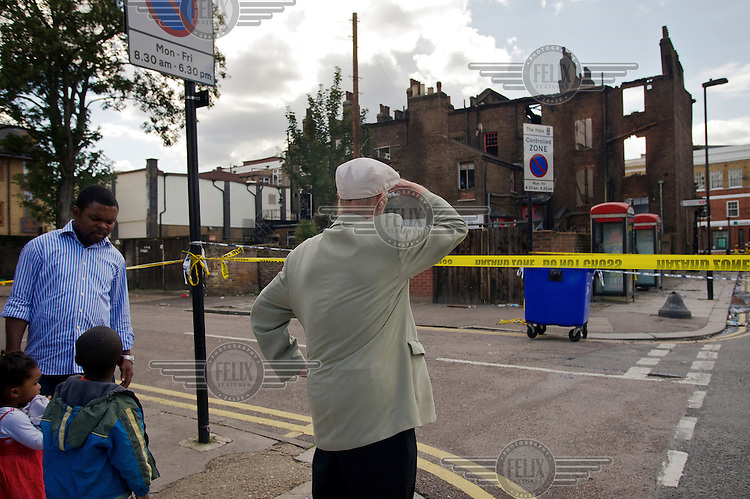 Local residents look out over a cordoned area and damaged buildings where rioting took place two nights earlier in Tottenham, London borough of Haringey. London saw the beginnings of riots on Saturday evening, after a peaceful protest in response to the shooting by police of Mark Duggan during an attempted arrest, escalated into violence. By the third night of violence, rioting had spread to many areas of the capital and to other cities around the country.