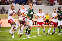 Jack Jewsbury (13) of the Portland Timbers attempts a back heel shot as Thierry Henry (14) and Kenny Cooper (33) of the New York Red Bulls defend. The New York Red Bulls  defeated the Portland Timbers 3-2 during a Major League Soccer (MLS) match at Red Bull Arena in Harrison, NJ, on August 19, 2012.
