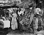 With a canvas tarpaulin for a church and packing cases for an altar, a Navy chaplain holds mass for Marines on Saipan in the Marianas. The service was held in memory of brave comrades who lost their lived in the initial landings on June 13, 1944.