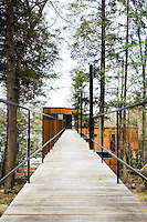The weathered decking on this contemporary footbridge leads visitors to the entrance and the roof terrace of this tree house by the lake
