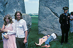 1970's Free festival at Stonehenge to celebrate the summer solstice June 21st 1975. Besides the hippies a small group of English tourists watched as others lay in the sun.