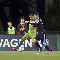 New England Revolution forward Milton Caraglio (9) dribbles as Seattle Sounders defender Patrick Ianni (4) defends. In a Major League Soccer (MLS) match, the Seattle Sounders FC defeated the New England Revolution, 2-1, at Gillette Stadium on October 1, 2011.