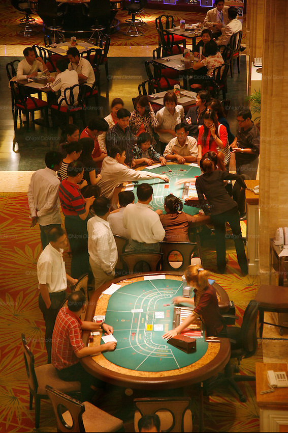 Phnom Penh's Nagaworld Casino and five-star hotel is one of Cambodia's biggest private employers with more than 3,000 staff catering for a stream of visitors. It functions non-stop 24 hours a day with an inside airconditioned controlled temperature of 21 degrees.It is a 14 storey hotel and entertainment complex, with more than 500 bedrooms, 14 restaurants and bars, 700 slot machines and 200 gambling tables. There is also a spa, karaoke and VIP suites, live bands, and a nightclub. Its monolithic building dominates the skyline at the meeting point of the Mekong and Tonle Sap rivers, in stark contrast to nearby intricate Khmer architecture.///Birds eye view over casino and gaming halls at Nagaworld with guests gambling