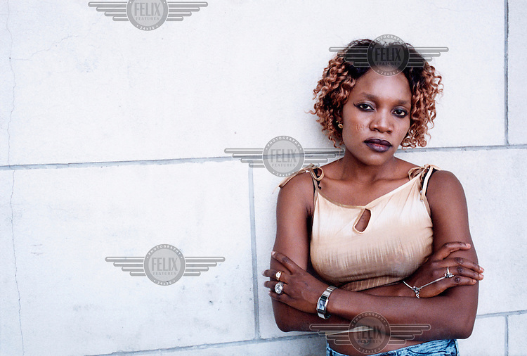 Portrait of Doris, a Nigerian prostitute. She sometimes works 18 hours a day. Thousands of Nigerian women are trafficked into Western Europe every year. They are forced to work in the sex industry to pay back debts of up to $50,000. Having entered Western Europe illegally, the women are pushed to the periphery of society. 95% of the trafficked Nigerian women come from Edo State (Southern Nigeria) where the traffickers have set up their networks.  .The traffickers (madams) control the women through the practice of Juju (voodoo) which is carried out on the girls before they leave Nigeria. The psychological . fear is real for the women. It is a strong spritual, religious tradition in southern Nigeria and is based on the unbreakable bedrock of faith. During the juju ceremony an oath of loyalty is signed between a god, the trafficker and the women. The god keeps the woman's spirit until the debt is paid.