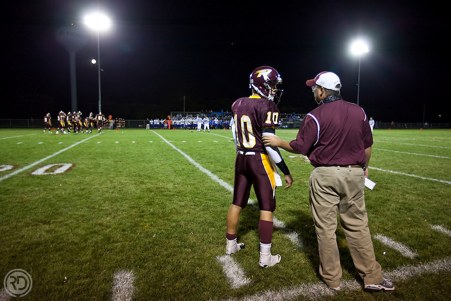 #10 Adam Pittser, QB.Richmond-Burton High School .September 24, 2010..Game Action and related activities at the Central HS @ Richmond-Burton HS varsity football game...Adam and his head coach, Patrick Elder talk during a time out...Photograph © Ross Dettman