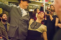 New Yorkers, tourists and subway buffs, some in period garb, dance during a vintage MTA Nostalgia Train Christmas season ride on Sunday, December 16, 2012. The straps, ceiling fans and rattan seats are a far cry from the plastic and air conditioning in modern subway cars. The Metropolitan Transit Authority has several of these trains for the various subway lines which they put into use for special occasions. The trains normally reside in the New York City Transit Museum in downtown Brooklyn where they can be visited every day.  © Frances M. Roberts)