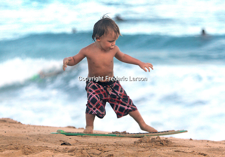 A boy demonstrates his technique in sanding on a skim board at Sandy Beach in Hawaii.
