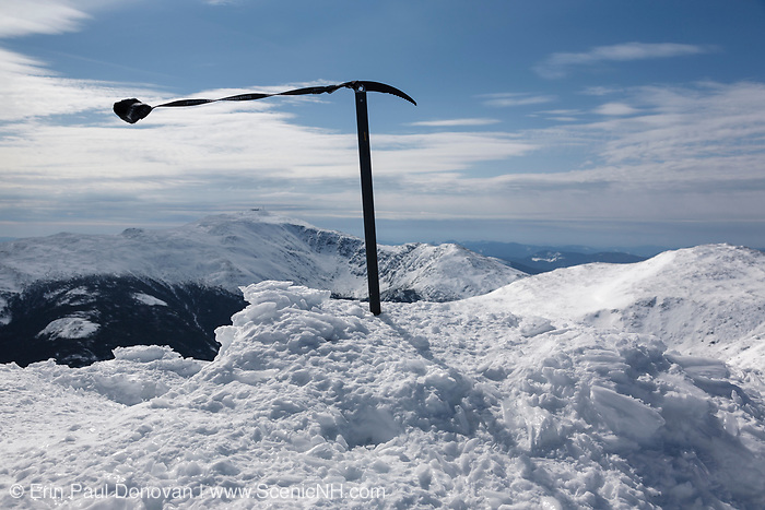The summit of Mount Adams during the winter months in the White Mountains, New Hampshire. Mount Washington is in the distance. Strong winds casue the leash on the ice axe to blow around.