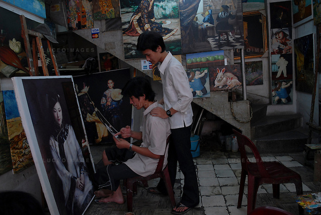 Painters copy artwork to sell to tourists in Ho Chi Minh City, Vietnam.