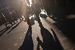 Amid afternoon crowds, a backlit romantic couple walk along Piccadilly holding hands.