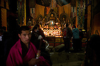 Pilgrims are making offerings of butter lamps in the temple of Maitreya -the buddha of  the Future- in the monastery of Labrang (Xiahe). Maitreya symbolizes the hope of better times.