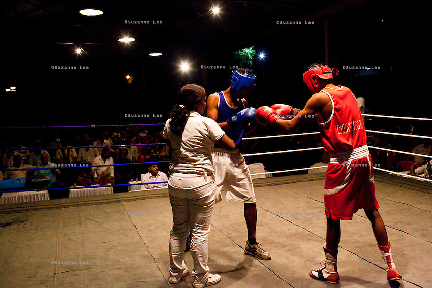 Razia Shabnam referees a bout at an all-India invitational boxing competition in the neighbouring town of Burnpur, Calcutta, West Bengal, India. Razia Shabnam, 28, was one of the first women boxers in Kolkata. She was also the first woman in her community to go to college. She is now a coach and one of only three international female boxing referees in India. Photo by Suzanne Lee for Panos London
