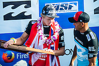 PIPELINE, Oahu/Hawaii (Saturday, December 14, 2013) Kelly Slater (USA) with John John Florence (HAW).- Kelly Slater (USA), 41, has won his 7th Billabong Pipe Masters in Memory of Andy Irons after a day of incredible 10-to-15 foot (three to four metre) waves at Pipeline today. Slater defeated John John Florence (HAW), 21, in a hard-fought, 35-minute Final that ended with less than half-a-point separating the two. The runner-up finish for Florence saw him crowned 2013 Vans Triple Crown of Surfing champion.<br /> <br /> The final day of the Billabong Pipe Masters capped off the 2013 ASP World Championship Tour (WCT) season in fine style, with epic conditions providing the ideal backdrop for the crowning of Mick Fanning (AUS), 32, as the ASP World Champion. It also finalized the ASP Top 34 roster for 2014. Fanning finished third overall, defeated by Florence in their Semifinal.<br /> With tens of thousands packing the beach at Pipeline, and the gravitas of Slater&rsquo;s 56th elite tour victory apparent, the greatest athlete the sport has ever produced was emotional on the final day of 2013.<br /> <br /> Fanning&rsquo;s road to the 2013 ASP World Title was nothing short of spectacular on the final day of competition. Finding himself behind during both his Round 5 and Quarterfinals bouts, the iron-nerved Australian nailed huge Pipeline scores in both occasions to take the heat wins and his third world surfing crown.<br /> <br /> &ldquo;I&rsquo;ve never put myself in the same circles as Tom Curren and Andy Irons,&rdquo; Fanning said. &ldquo;Tom (Curren) is such an enigma and was so instrumental to injecting style into our sport. Andy (Irons)&hellip;what hasn&rsquo;t been said about Andy? He was such a legend and he was such a good friend. I&rsquo;m honored to be a part of this group. I was happy with one title and I was overwhelmed with two. With three? I don&rsquo;t have words for that.&rdquo;<br /> <br /> Today marked John John Florence&rsquo;s second Vans Triple Crown Title, but his runner-up in the final event forces him to hang on to his life-long dream of one day hoi