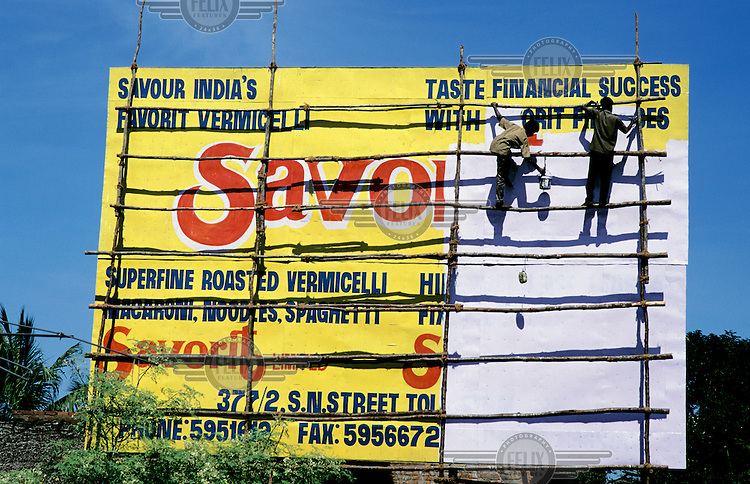 Advertising hoarding being hand painted.