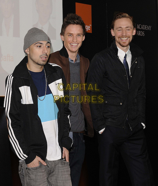 Adam Deacon, Eddie Redmayne & Tom Hiddleston.The Orange Wednesday Rising Star Award nominations launch, BAFTA, Piccadilly, London, England..January 11th, 2012.half length black suit jacket grey gray beanie hat brown goatee facial hair.CAP/CAN.©Can Nguyen/Capital Pictures.
