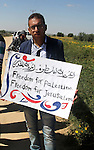 Palestinians hold banners during a rally to mark Land Day  held in the village of Abassan, east of Khan Yunis near the border fence between Israel and the southern Gaza Strip on March 31, 2015. On the annual Land Day, demonstrations are held to remember six Arab Israeli protesters who were shot dead by Israeli police and troops during mass protests in 1976 against plans to confiscate Arab land in the Galilee. Photo by Abed Rahim Khatib