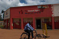 A cyclist passes one of many buildings branded with a mobile network's colours.