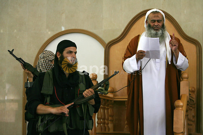"Abdel Latif Musa, a representative the radical Palestinian Islamist group Jund Ansar Allah, is guarded by an armed member of his radical group as he delivers the Friday prayer sermon at a mosque in the southern Gaza Strip town of Rafah on August 14, 2009. Islamic radicals from an al-Qaida-inspired group, Jund Ansar Allah, or the Soldiers of the Companions of God, defied Gaza's Hamas rulers by declaring the territory an ""Islamic emirate"" at Friday prayers. Shortly after, a gunbattle broke out between the militants in the mosque and Hamas forces which killed about 22 and injured more than 200 about 40 of them are criticaly. Photo By Abed Rahim Khatib"