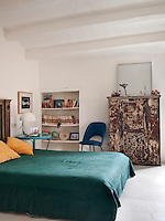 The bedroom is furnished with a large distressed cabinet and a retro blue chair and sidetable