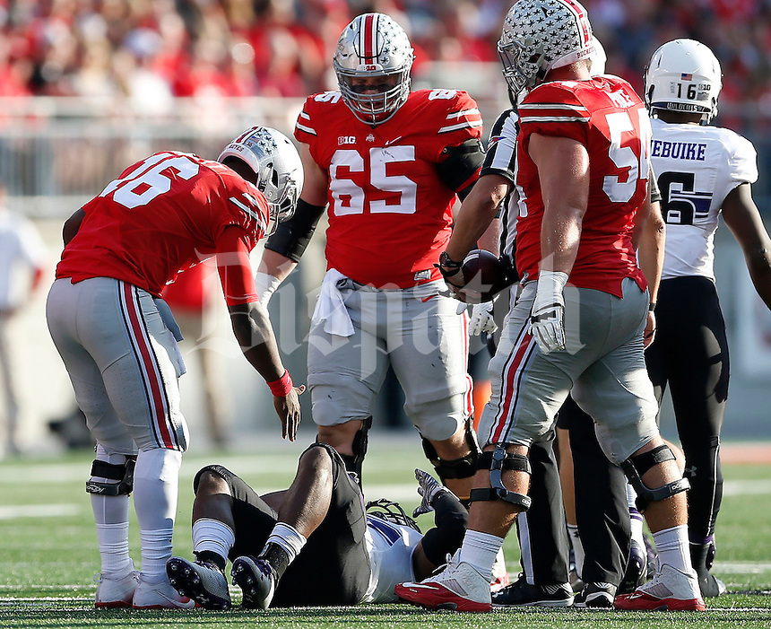 Ohio State Buckeyes quarterback J.T. Barrett (16) offers to help up Northwestern Wildcats linebacker Anthony Walker Jr. (1) during the second quarter of the NCAA football game between the Ohio State Buckeyes and the Northwestern Wildcats at Ohio Stadium on Saturday, October 29, 2016. (Columbus Dispatch photo by Jonathan Quilter)